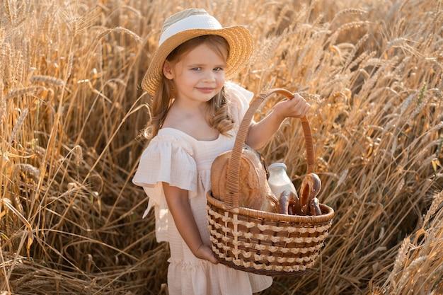 Маленькая блондинка в соломенной шляпе держит корзину с хлебом на пшеничном поле, экологически чистые сельскохозяйственные продукты