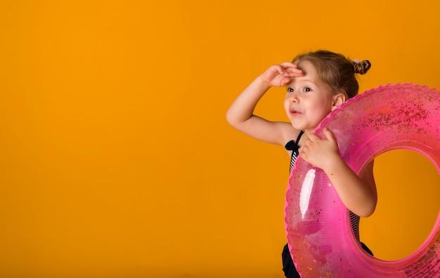 노란색 배경에 동그라미를 들고 수영복에 작은 금발 소녀