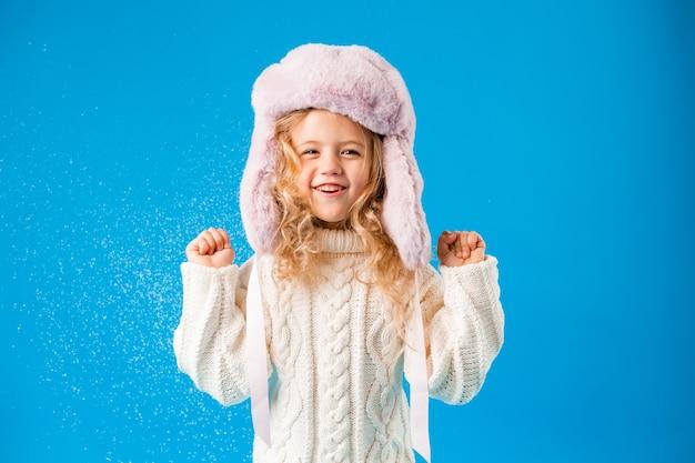 Маленькая блондинка в зимней одежде сдувает снег с рук
