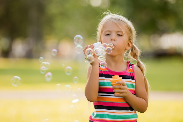 Little blonde girl inflates soap bubbles in summer on a walk
