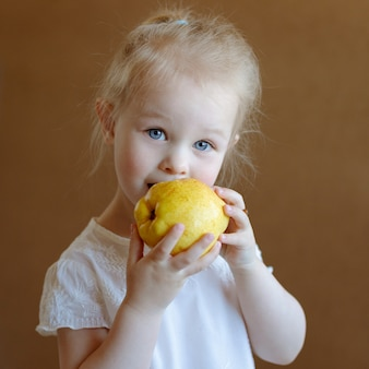 The little blonde girl is eating a yellow pear