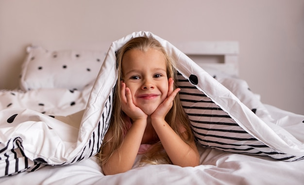 A little blonde girl is lying under a blanket on the bed in the room