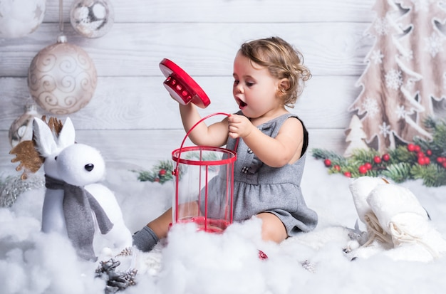 Little blonde girl is playing in christmas winter decoration.