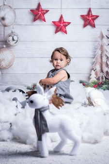 Little blonde girl is posing in christmas winter decoration.