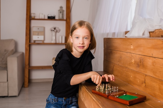 A little blonde girl is sitting and playing chess on a board. a logic game