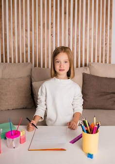 A little blonde girl is sitting at a table and drawing on paper. art for children