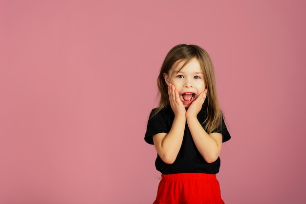 Little blonde girl is very surprised . a child shouting wow holds his face in amazement. copyspace