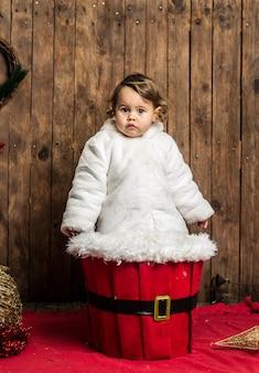 Little blonde girl is wearing a white coat on wood