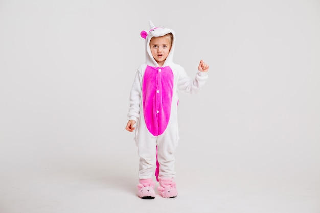 Little blonde girl in kigurumi on white background