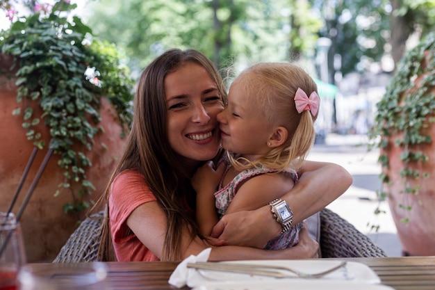 어린 금발 소녀가 식당에서 주문을 기다리는 엄마에게 키스합니다.