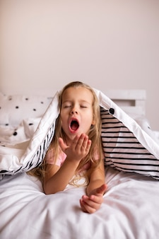 A little blonde girl lies under the blanket and yawns on the bed in the room