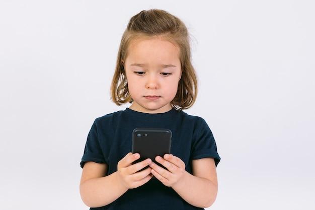 Маленькая блондинка, глядя на свой мобильный телефон