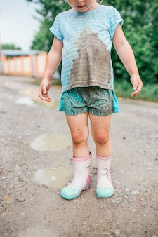 Little blonde girl looks at her dirty clothes after fall into a puddle.