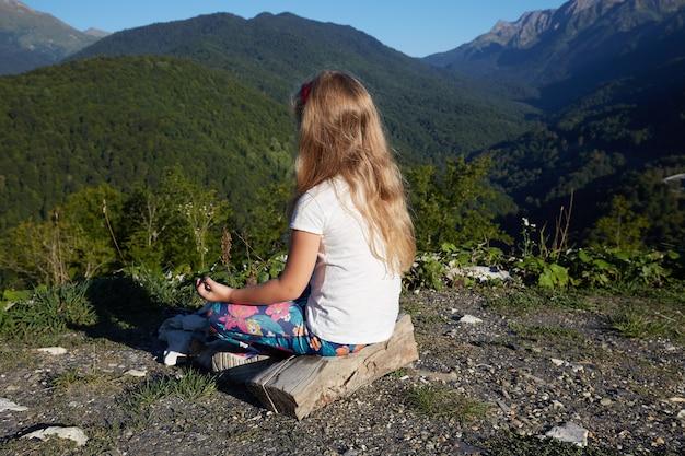 Маленькая блондинка медитирует на вершине горы.