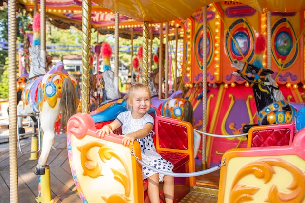 Little blonde girl on old french carousel in a holiday park. charming cute little girl in a dress is smiting and enjoy.