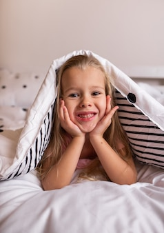 A little blonde girl in pajamas is lying on cotton bed linen on the bed