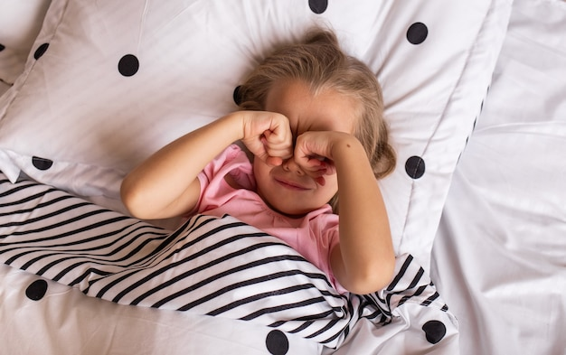 A little blonde girl in pajamas wakes up in bed and rubs her eyes with her hands