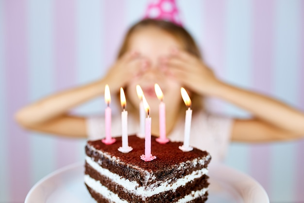 Little blonde girl in pink birthday cap smiling close her eyes make a wish