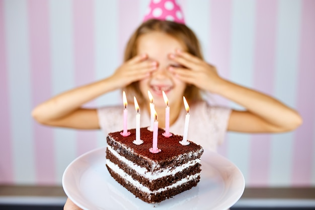 Little blonde girl in pink birthday cap smiling, close her eyes, make a wish