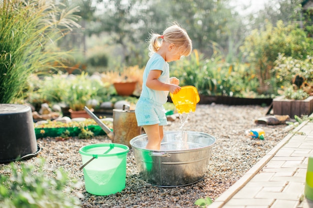 Little blonde girl playing at garden with water in a tin basin. kids gardening. summer outdoor water fun. childhood in the country
