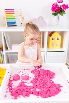 Маленькая белокурая девушка играя с розовым волшебным песком на белой таблице в светлой комнате. сенсорное развитие. уроки в детском саду.