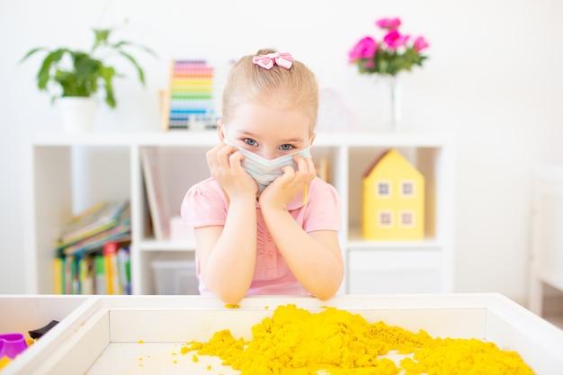 Маленькая белокурая девочка играет с желтым кинетическим песком дома, надев медицинскую маску для лица, чтобы защитить себя от вируса