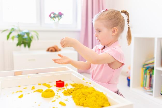 Маленькая белокурая девушка играя с желтым волшебным песком на белой таблице в светлой комнате. сенсорное развитие. уроки в детском саду.