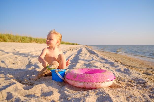 Маленькая блондинка играет на песке на пляже в солнечный день рядом с надувным кольцом