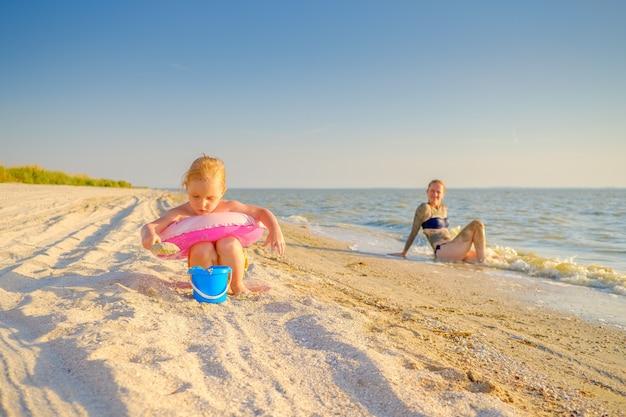 Маленькая блондинка играет в песке на берегу моря. на заднем плане мама малыша отдыхает и загорает у воды. семейный отдых на море.