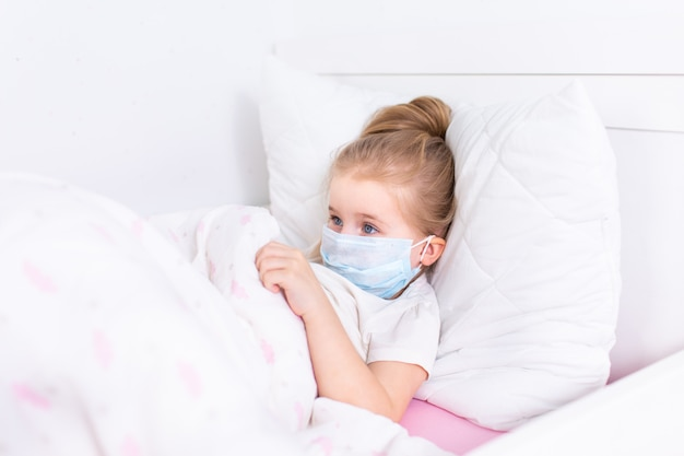 Little blonde girl in protective medical mask lying in white bed in a white room.