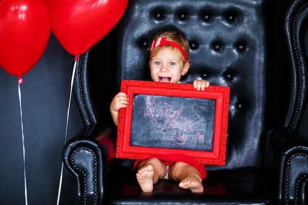 Little blonde girl in red dress with red wreath with hearts sitting on the armchair with red heart balloon on the st. valentine's day.