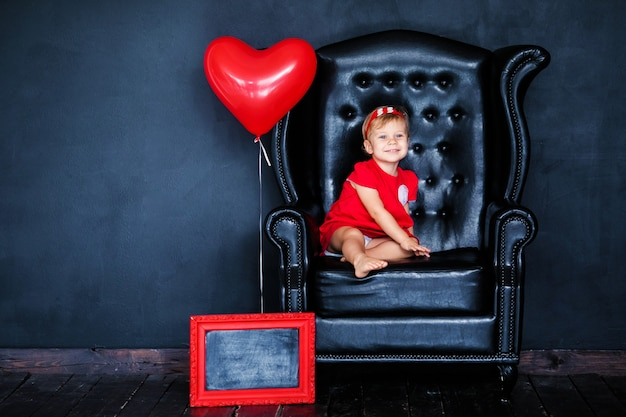 Little blonde girl in red dress with red wreath with hearts sitting on the armchair