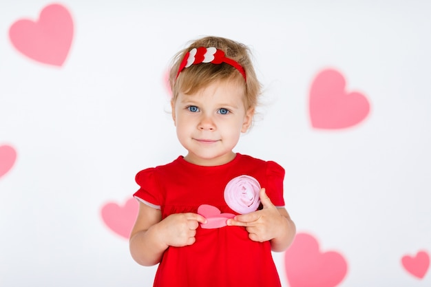 Little blonde girl in red dress with red wreath with hearts on white with pink hearts on the  valentines day