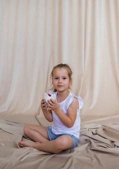 어린 금발 소녀는 베이지색 배경에 촛불이 있는 축제 컵케이크를 들고 공간 사본을 들고 있다