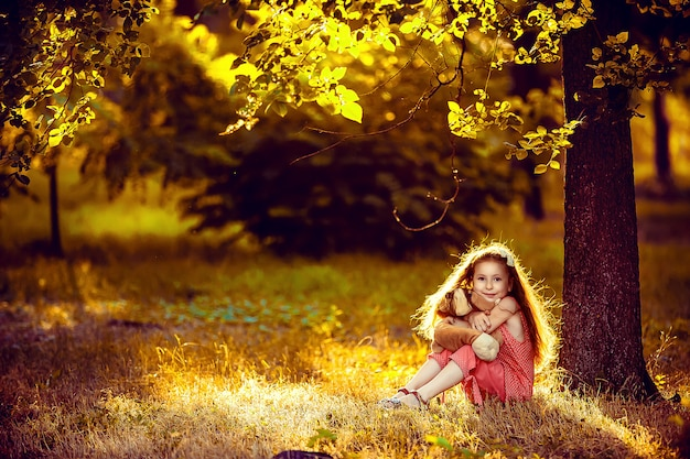 Little blonde girl sitting under a birch tree with a toy