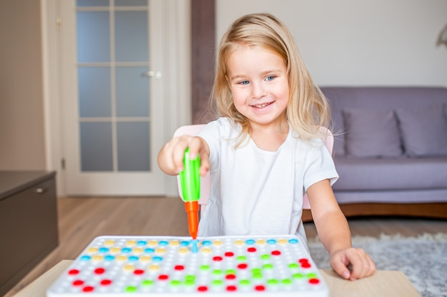 Little blonde girl sitting at a table at home playing with a toy screwdriver and multicolor screws. early education.