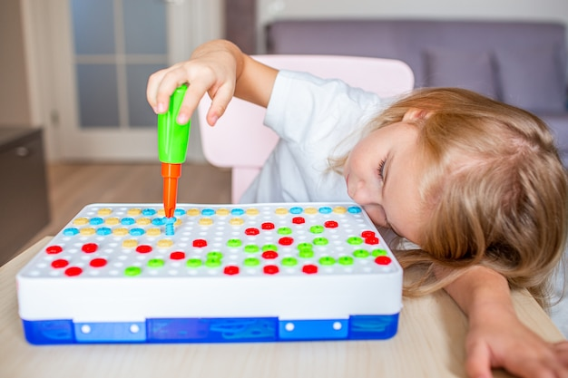 Little blonde girl sitting at a table at home playing with a toy screwdriver