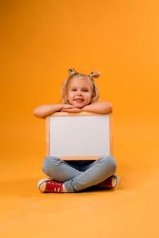 Маленькая блондинка улыбается и держит пустую чертежную доску, место для текста
