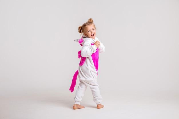 Маленькая белокурая девушка усмехаясь в kigurumi на пустом пространстве