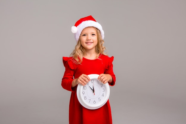 Little blonde girl smiling in santa suit with white clock