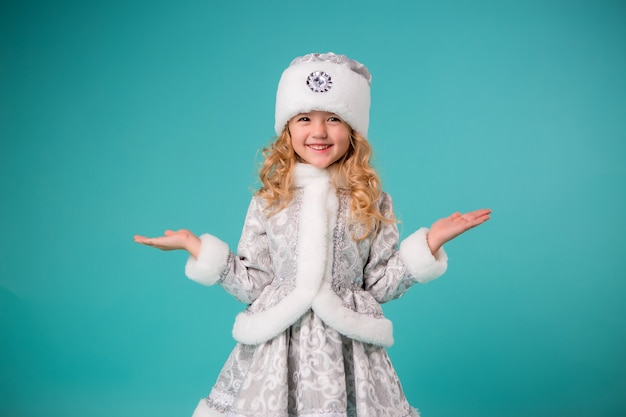Little blonde girl smiling in snow maiden costume isolate on blue wall