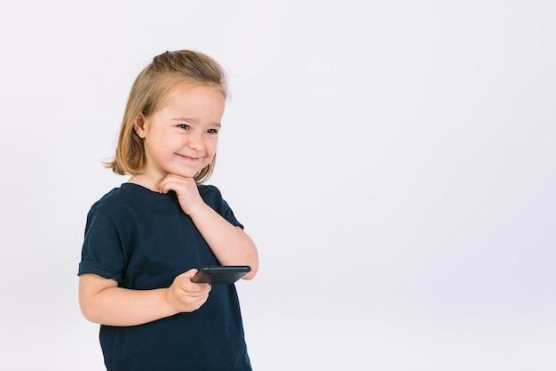 Маленькая блондинка улыбается со своим мобильным телефоном