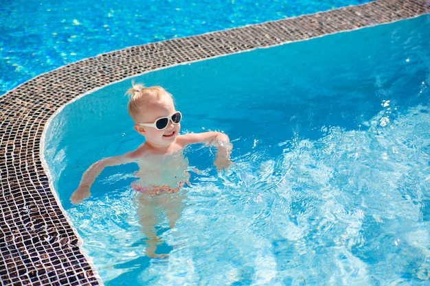 A little blonde girl splashing in the pool with clear water in the summer.