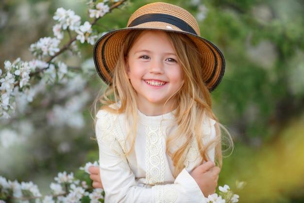 Little blonde girl in a straw hat near a flowering tree