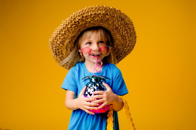 Little blonde girl in a straw hat and sunglasses is smiling on a yellow background
