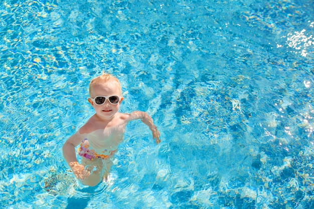Little blonde girl swims in the pool with blue water