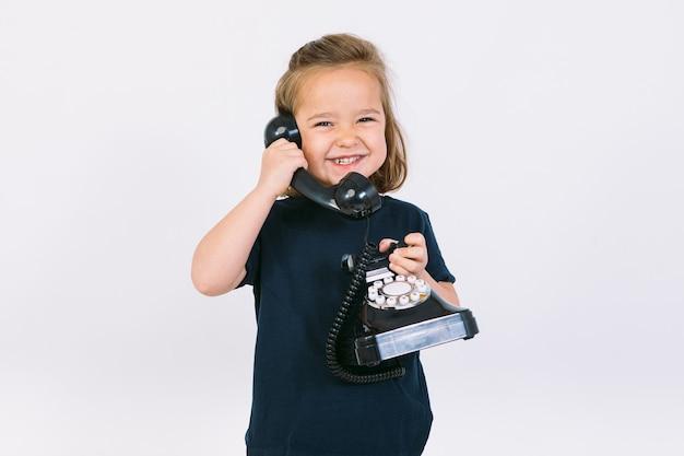 Маленькая блондинка разговаривает по своему ретро-телефону