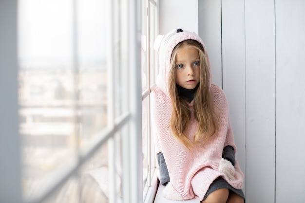 Little blonde girl wearing pink pullover