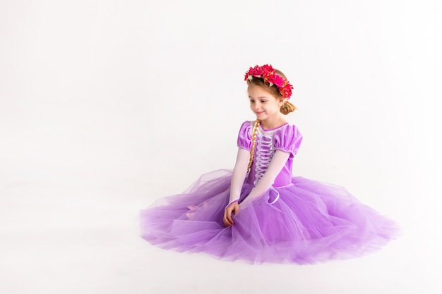 Little blonde girl wearing purple fairy princess dress on white background. kids costume for new year party