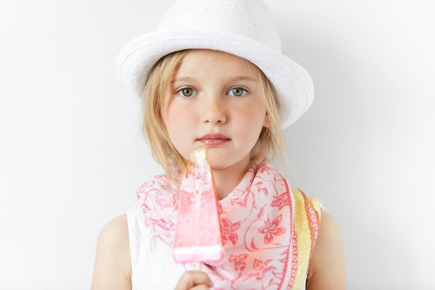 白い帽子をかぶっているとアイスクリームを食べる金髪少女